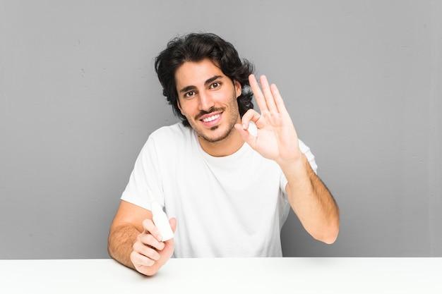 Молодой человек держа брызг носа жизнерадостный и уверенно показывая одобренный жест.
