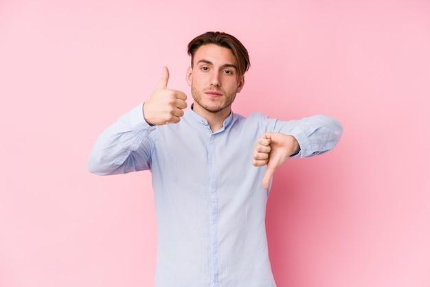 ピンクの背景でポーズをとって親指を示す若い白人男と親指ダウン、難しいコンセプトを選択