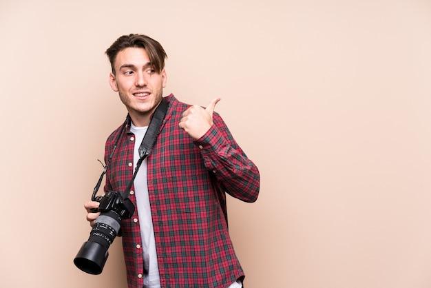 若い白人写真家の男は、親指の指で離れて、笑って屈託のないポイントを分離しました。