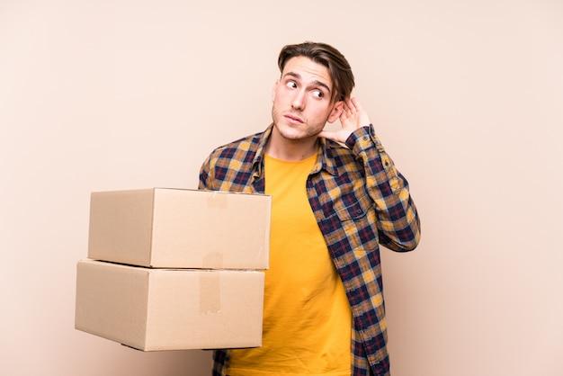 Молодой кавказский человек держа коробки пробуя слушать сплетню.
