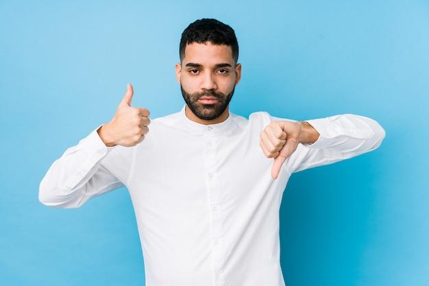 分離された青い背景に対して若いラテン男分離親指を表示、親指、難しい選択の概念