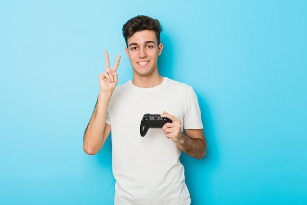 Молодой кавказский человек играя видеоигры с регулятором игры показывая номер два с пальцами.