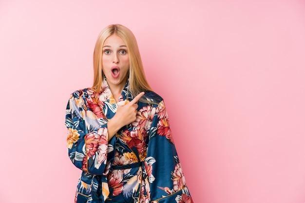 Молодая блондинка в пижаме кимоно, указывая в сторону