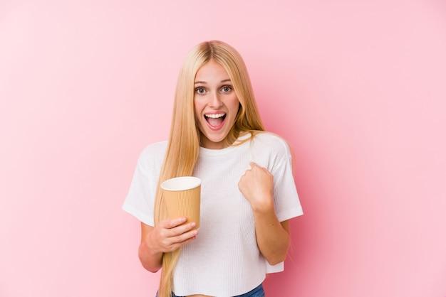 テイクアウトコーヒーを保持している若いブロンドの女の子は、自分自身を指して驚いて、広く笑っています。