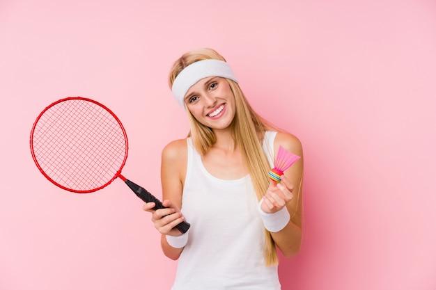 Молодая белокурая женщина играя изолированный бадминтон