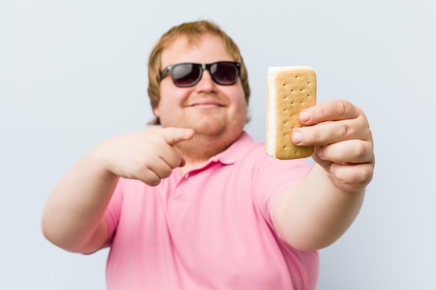 Кавказский сумасшедший блондин толстый мужчина держит мороженое