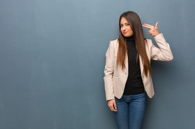 自殺ジェスチャーを行う若いビジネス女性