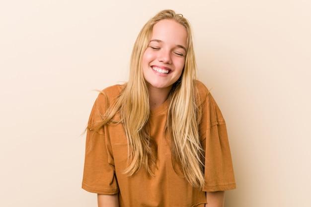 Милая и натуральная девушка-подросток смеется и закрывает глаза, чувствует себя расслабленной и счастливой.