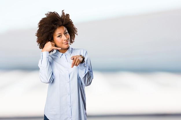 Молодая черная женщина, делая телефонный жест