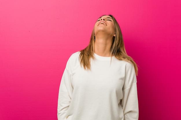 リラックスした壁と幸せな笑いの壁に対して若い本物のカリスマ的な本物の女性、首を伸ばして歯を見せて。