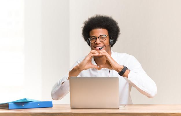 Молодой телемаркетер черный человек делает форму сердца с руками