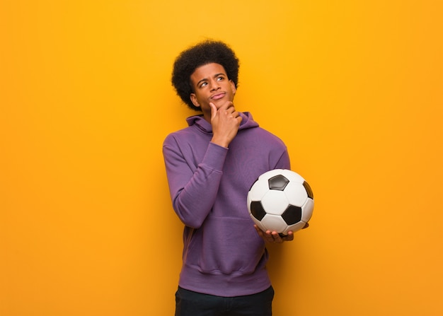 Молодой человек спорта афроамериканца держа футбольный мяч сомневаясь и смущенный