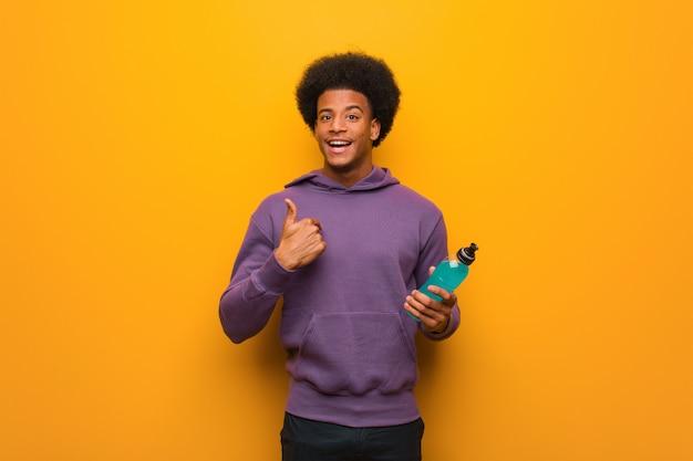 エネルギードリンクを保持している若いアフリカ系アメリカ人フィットネス男は驚いて、成功と繁栄を感じています