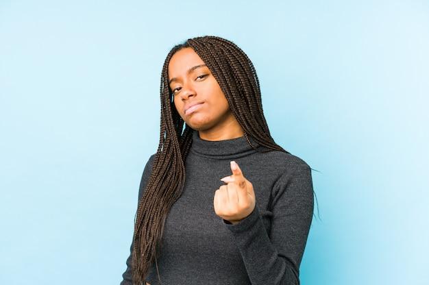 若いアフリカ系アメリカ人女性は、あなたを指で指している青色の背景に分離されて、まるで招待が近づくように。