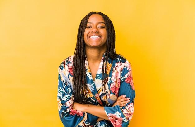 アジアのピジャマを身に着けている若いアフリカ系アメリカ人女性は笑って、楽しんで分離しました。