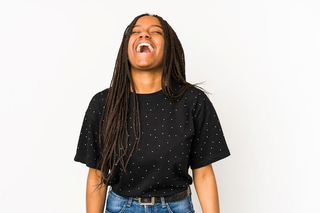 リラックスして幸せな白い背景に分離された若いアフリカ系アメリカ人女性は笑って、首を伸ばして歯を見せて。