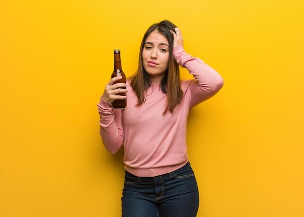 ビールを持って若いかわいい女性が心配し、圧倒