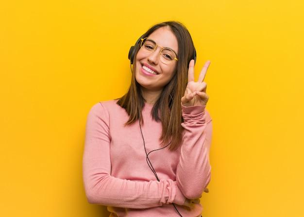 Молодая милая женщина слушая к музыке показывая номер два