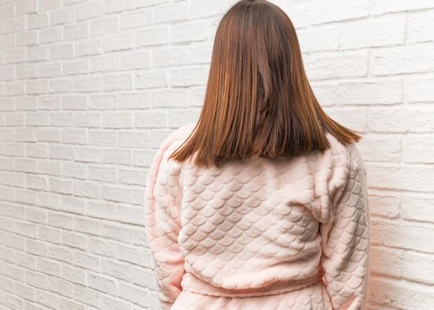 Молодая женщина в пижаме сзади, оглядываясь назад