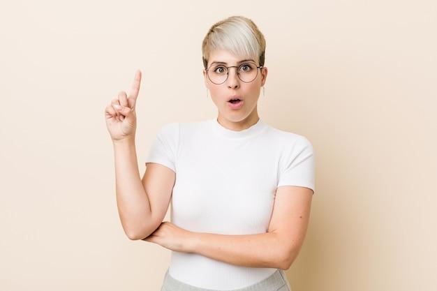 Молодая подлинная естественная женщина нося белую рубашку имея некоторую отличную идею, концепцию творческих способностей.
