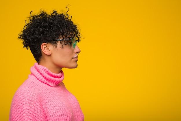 左を見つめるピンクのセーターを着た若いアフリカ系アメリカ人女性、横向きのポーズ。