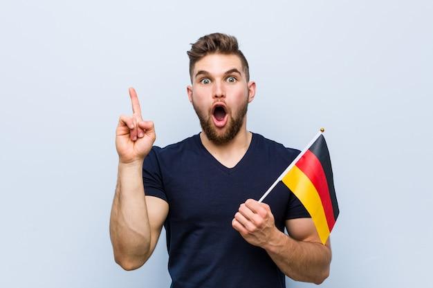 いくつかの素晴らしいアイデア、創造性の概念を持つドイツの旗を保持している若い白人男。