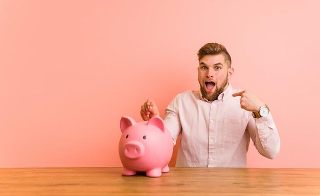 貯金箱に座っている若い白人男は、自分自身を指して驚いて、広く笑っています。