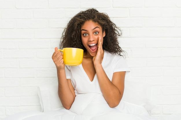 叫んでコーヒーマグカップを保持しているベッドの上に座っている若いアフリカ系アメリカ人女性は前に興奮しています。
