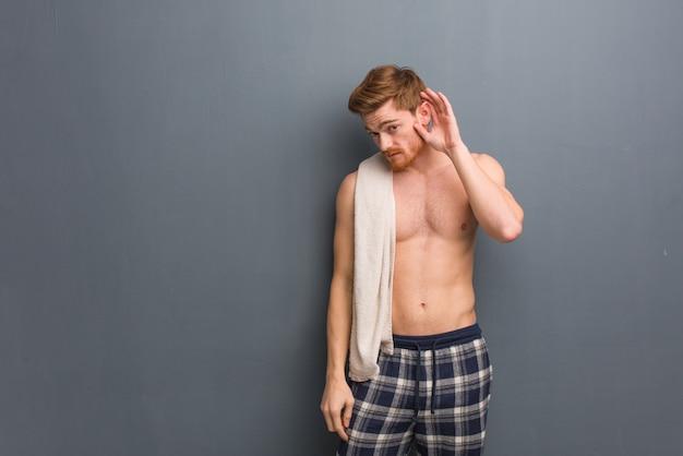 Молодой рыжий мужчина держит полотенце попытаться прослушать сплетни. он держит белое полотенце.