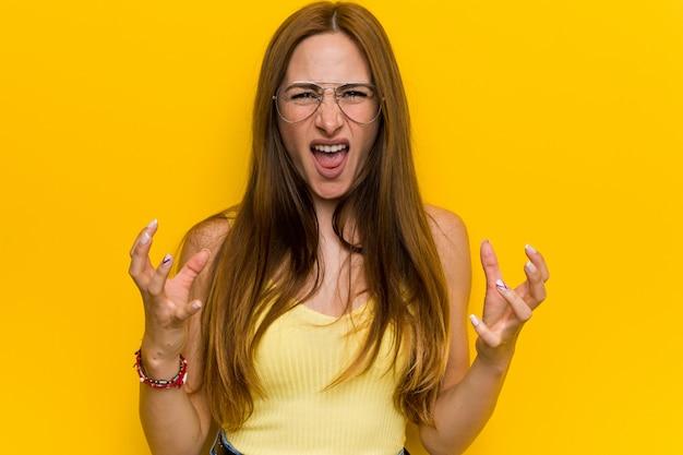 Рыжая молодая рыжая женщина с безупречной расстроен, кричать с напряженными руками.