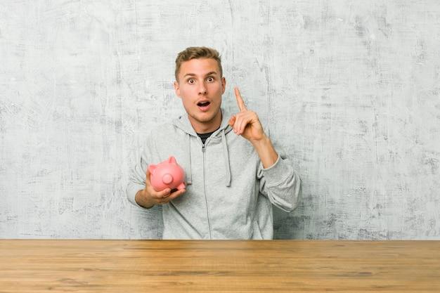 Деньги сбережений молодого человека при копилка имея идею, концепцию воодушевленности.