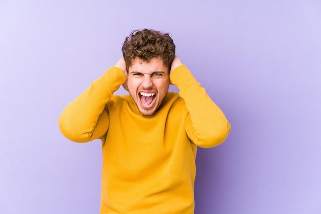 若いブロンドの巻き毛の白人男性は、あまりにも大きな音が聞こえないようにしようと手で耳を覆って分離しました。
