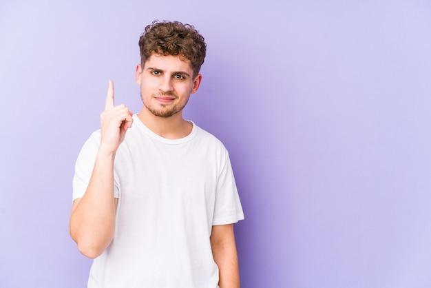 Человек молодого белокурого вьющиеся волосы кавказский изолировал показывать номер один с пальцем.