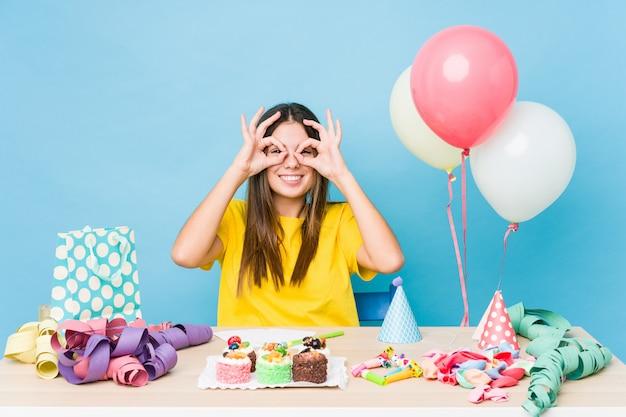 Молодая женщина организует день рождения, показывая хорошо знаком над глазами