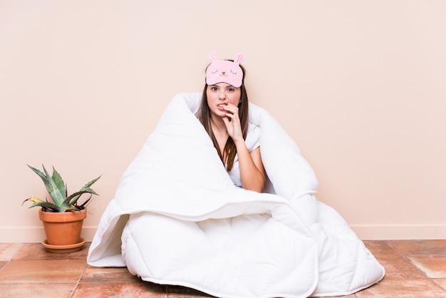神経質で非常に不安の爪をかむキルトで休む若い女性
