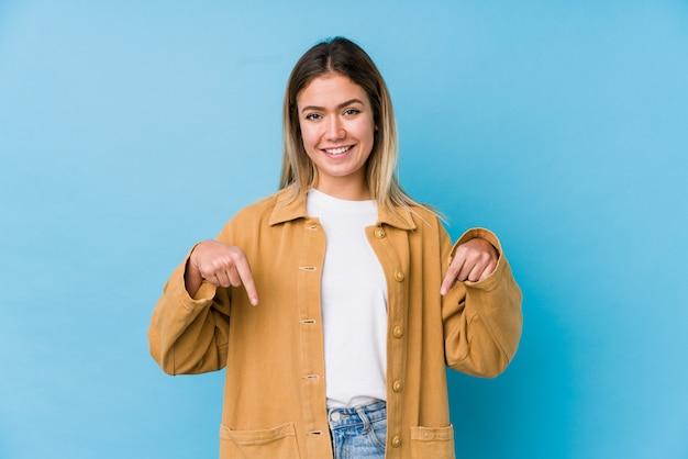Молодая женщина указывает пальцами вниз, положительное чувство