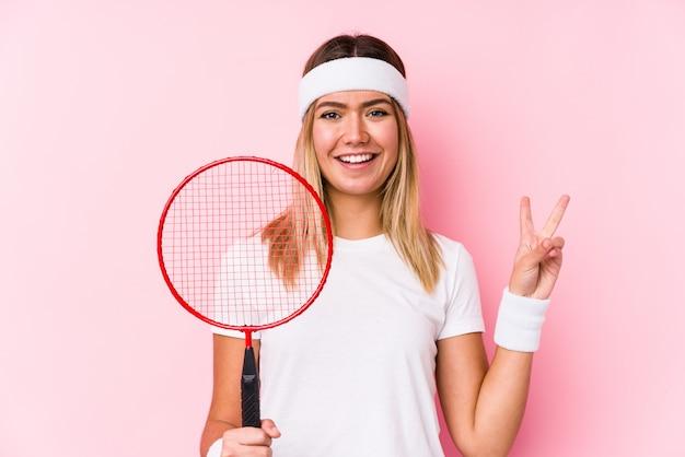 指で平和のシンボルを示すうれしそうな屈託のないバドミントンを演奏若い女性
