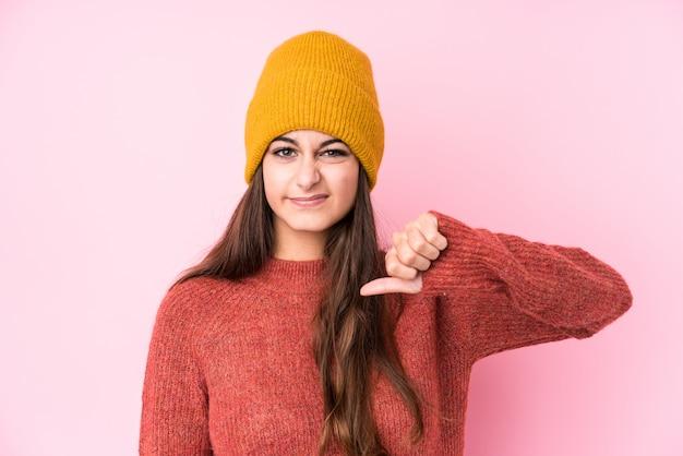 Молодая женщина в шерстяной шапке, показывая жест неприязни, пальцы вниз