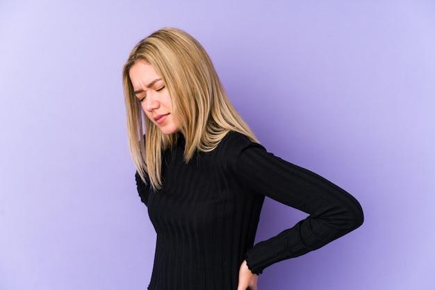 背中の痛みに苦しんでいる若いブロンドの女性