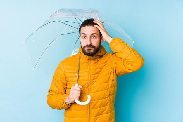 ショックを受けている傘を持って長い髪の外観を着ている若い男は、彼女は重要な会議を覚えている
