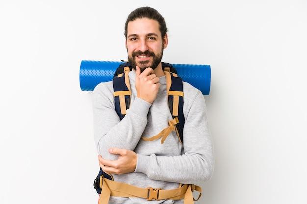 Молодой рюкзаком человек улыбается счастливым и уверенным, касаясь подбородка рукой