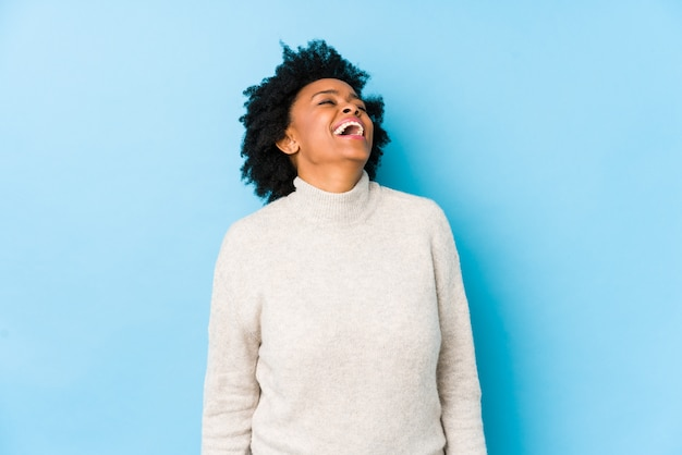 Женщина средних лет расслаблена и счастлива смеяться, шея растянута, показывая зубы