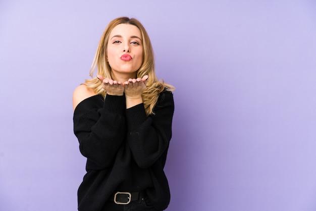 Молодая блондинка складывает губы и держит ладони, чтобы отправить воздушный поцелуй