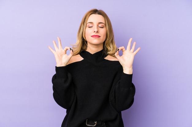 Молодая блондинка расслабляется после тяжелого рабочего дня, она выполняет йогу