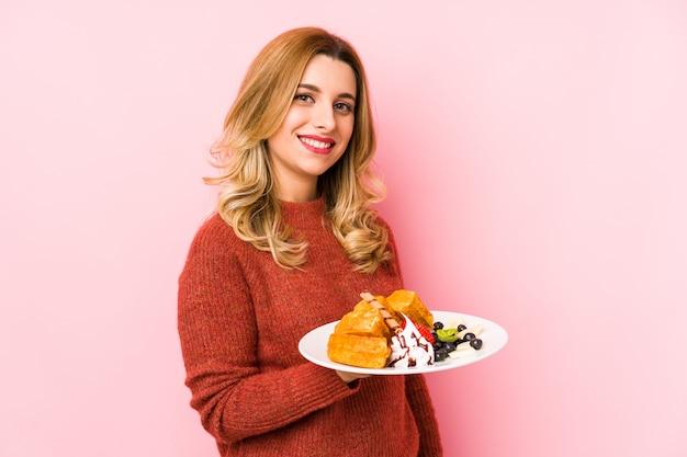 ワッフルデザートを食べる若いブロンドの女性は笑顔、陽気で快適な脇に見える