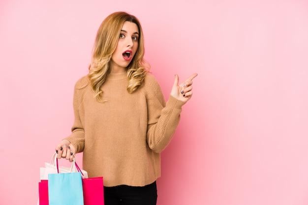 側を指している買い物袋を保持している若いブロンドの女性