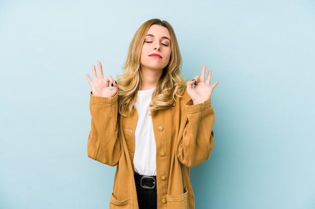 Молодая блондинка красотка расслабляется после тяжелого рабочего дня, она выполняет йогу
