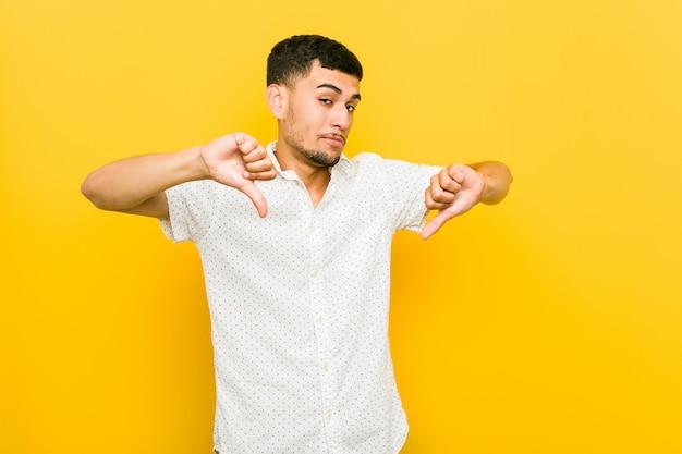 親指ダウンを示すと嫌悪感を表現する若い男