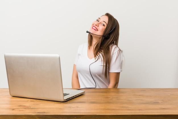 Молодая женщина телемаркетер смотрит в сторону, улыбаясь, веселый и приятный