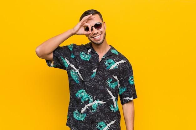 Молодой человек в летней одежде взволнован, держась за жест